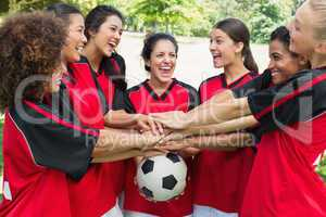 Excited soccer team stacking hands on ball