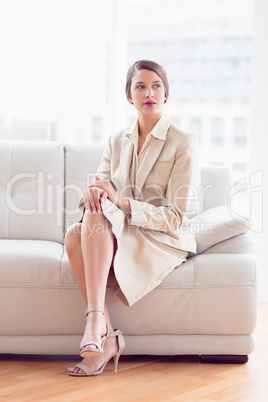 Stylish thoughtful businesswoman sitting on sofa