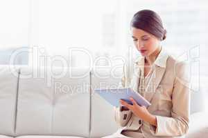 Stylish businesswoman sitting on sofa using tablet pc