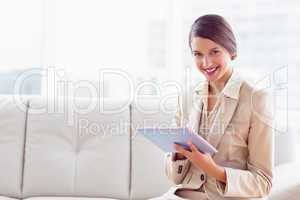 Stylish businesswoman sitting on sofa using tablet smiling at ca