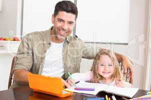 Happy little girl colouring at the table with her father