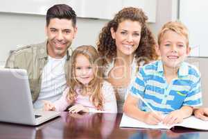 Happy parents colouring and using laptop with their young childr