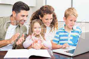 Happy parents using laptop with their young children
