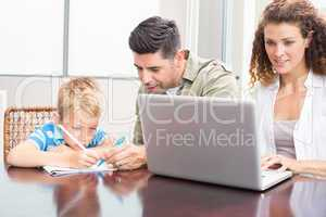 Father and son colouring with mother using laptop