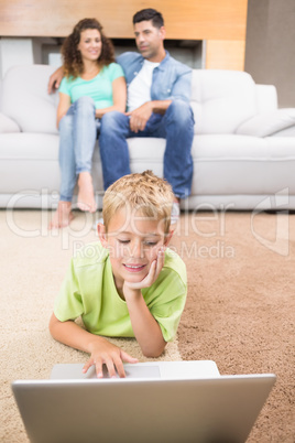 Cute little boy using laptop on the rug with parents sitting sof