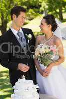 Newlywed couple with wedding cake at park