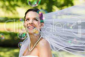 Beautiful bride looking at soap bubbles in park