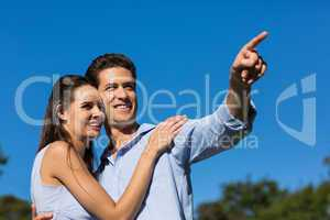 Couple looking away against clear blue sky