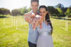 Young couple pointing finger to the camera at park