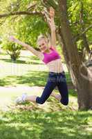 Full length of woman in sportswear jumping at park