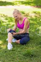 Healthy and beautiful woman in sportswear sitting in park