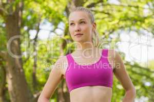 Healthy and beautiful woman in sports bra against trees in park