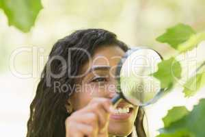 Woman examining leaves with magnifying glass