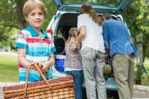 Boy with picnic basket while family in background at car trunk