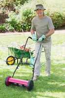 Smiling man mowing lawn