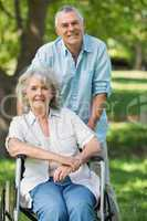 Mature man with woman sitting in wheel chair at park