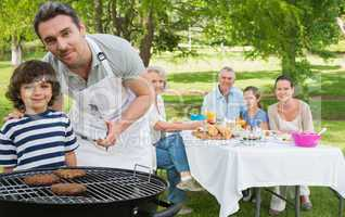 Father and son at barbecue grill with family having lunch in par