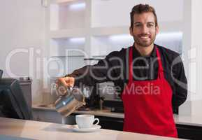 Smiling barista pouring milk into cup of coffee looking at camer