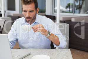 Concentrating businessman working with laptop drinking coffee