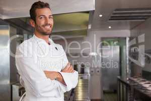 Smiling young chef standing with arms crossed