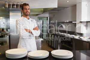 Smiling young chef standing with arms crossed behind counter