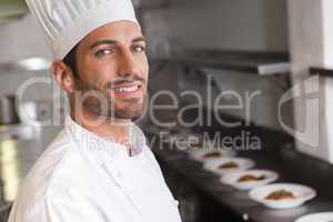 Cheerful young chef smiling at camera