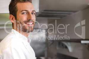 Cheerful young chef looking at camera