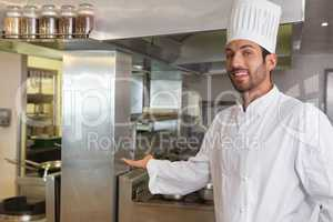Smiling young chef looking at camera showing his workplace