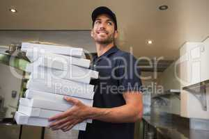 Smiling pizza delivery man holding many pizza boxes