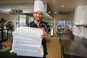 Smiling pizza chef holding stack of pizza boxes