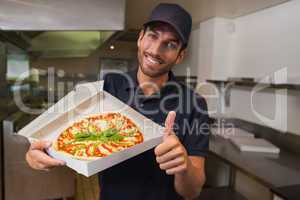 Happy pizza delivery man showing fresh pizza and thumbs up