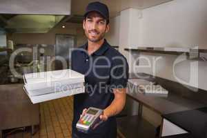 Smiling pizza delivery man holding credit card machine