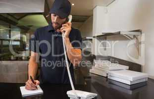 Handsome pizza delivery man taking an order over the phone