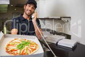 Smiling pizza delivery man taking an order over the phone showin