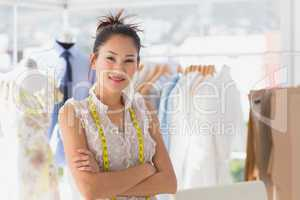 Portrait of a beautiful female fashion designer with rack of clo