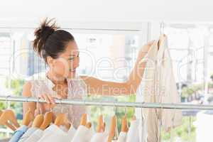 Fashion designer looking at shirt beside rack of clothes
