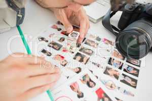 Concentrate male artist sitting at desk with photos