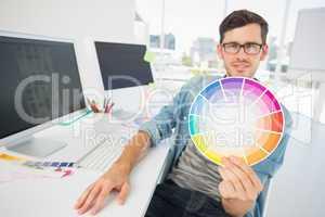 Male artist holding color wheel at desk