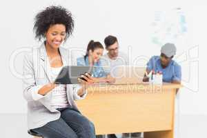 Artist using digital tablet with colleagues in background at off