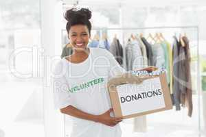 Smiling young woman with clothes donation