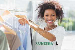 Smiling female volunteer by clothes rack