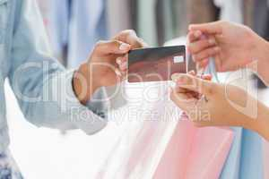 Mid section of customer receiving shopping bags and credit card