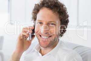 Closeup portrait of a smiling man using mobile phone