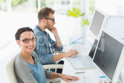 Team of young designers working at desk with woman smiling at ca
