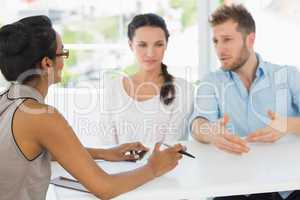 Therapist speaking with couple sitting at desk