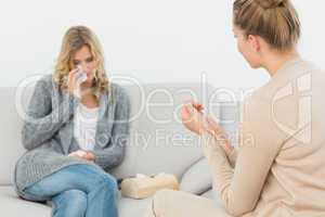 Therapist listening to crying patient on the sofa
