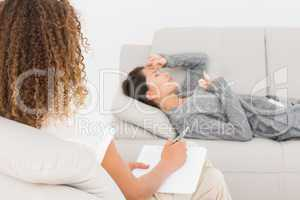 Therapist writing notes on her crying patient on the couch