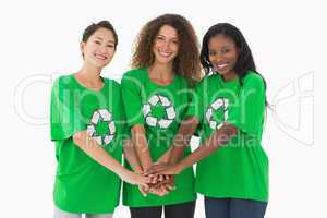Team of environmental activists smiling at camera with hands tog