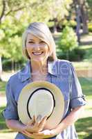 Woman holding sunhat in park