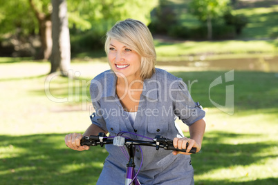Woman riding bicycle in parkland